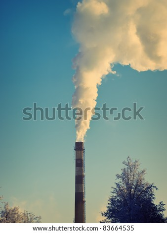 Smokestack with smoke over the blue sky - stock photo