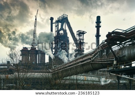 Smokestacks in factory with yellow smoke and clouds - stock photo