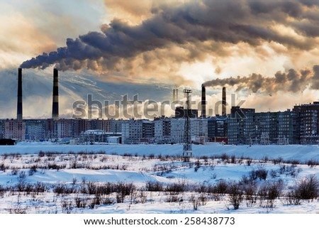 Smokestacks polluting the air over the city. Winter landscape. - stock photo