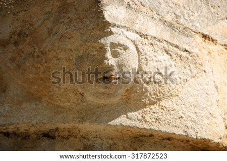 Smoking addiction. Stone human face (old building architectural detail) with real cigarette in the mouth.  - stock photo