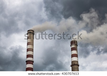 Smoking big industrial chimneys in dark clouds. Concept for environmental protection - stock photo