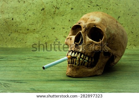 Smoking can kill you. Still Life with a Skull concept - stock photo