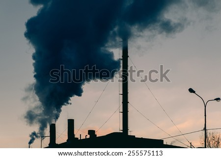 Smoking chimney of heating plant. Toned sunset image. - stock photo