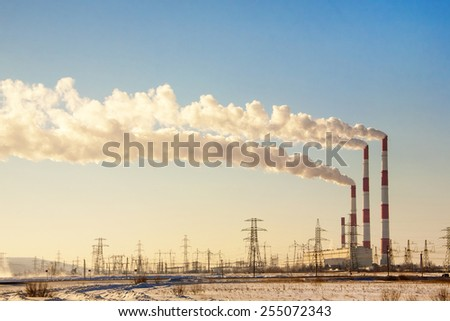 Smoking chimneys against the blue sky - stock photo