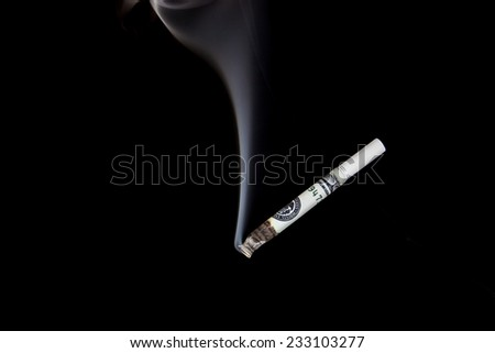 Smoking cigarette made from 100 dollar bills isolated on a black background - stock photo