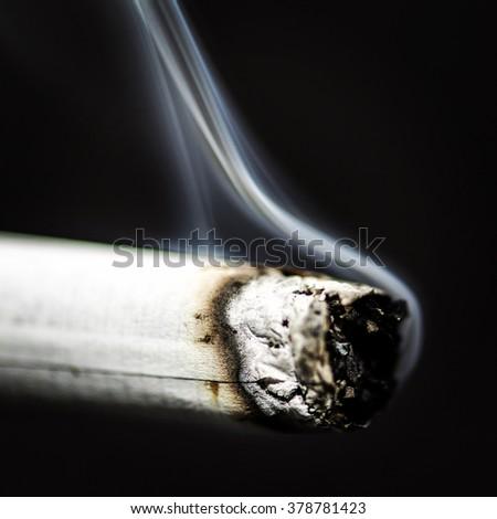 Smoking cigarette on a black background  - stock photo