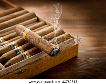 smoking cuban cigar over box  on wood background - stock photo