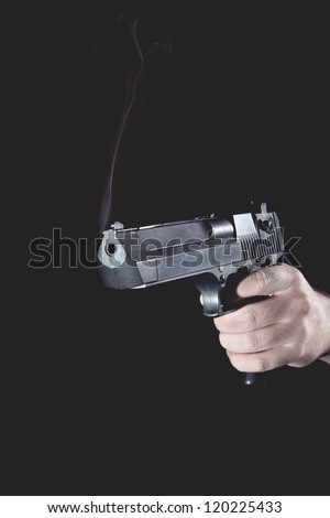 smoking gun after the shot in the hand of man - stock photo