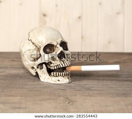 Smoking human skull with cigarette - stock photo