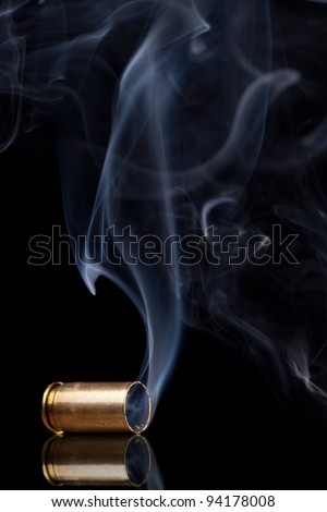 Smoking 9mm bullet casing over black background - stock photo