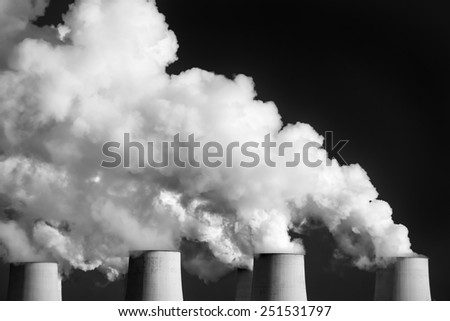 Smoking pipes of thermal power plant against blue sky on sunset,  /black and white/ - stock photo