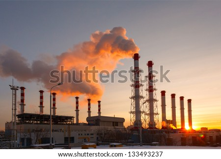 Smoking pipes of thermal power plant against sunrise - stock photo
