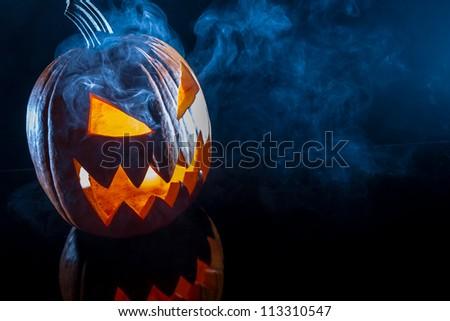 Smoking scary halloween pumpkin head - stock photo