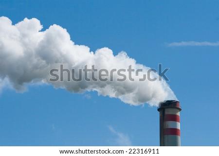 smoking smokestack with blue sky - stock photo