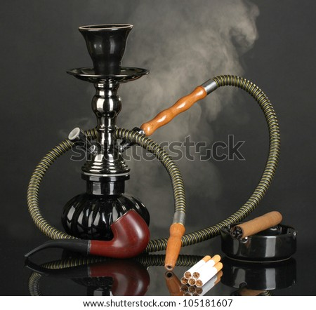 Smoking tools - a hookah, cigar, cigarette and pipe on black background - stock photo