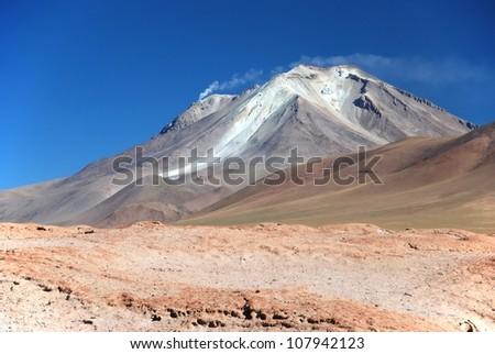 smoking volcano in the bolivian desert - stock photo