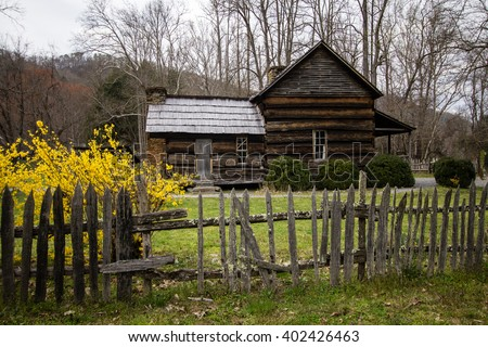 Smoky Mountain Cabin In The Spring. Historical cabin in the Smoky Mountains with spring forsythia in the foreground. This is a public structure in national park and not a privately owned residence. - stock photo