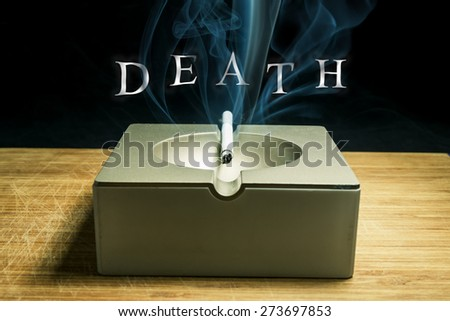 """Smoldering cigarette in the ashtray with the inscription of smoke """"death"""" close-up - stock photo"""
