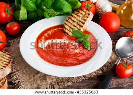Smooth and sweet tomato soup, seasoned with basil, garlic - stock photo