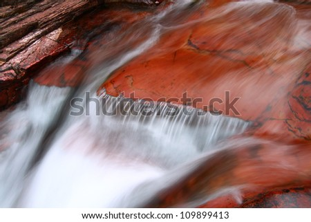 Smooth cascade over red rock in Glacier National Park of Montana - stock photo