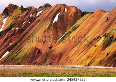 Smooth orange rhyolite mountains in Landmannalaugar nature reserve. In the hollows is last year's snow - stock photo