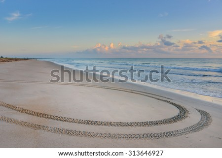 smooth sandy florida beach with tire tracks at sunrise, as background image with copy space - stock photo