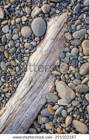 Smooth stones on driftwood at Ruby Beach, Olympic Peninsula, Olympic National Park, Washington - stock photo