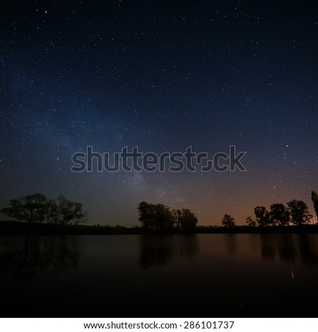 Smooth surface of forest lake on a background of the night sky and the Milky Way. - stock photo