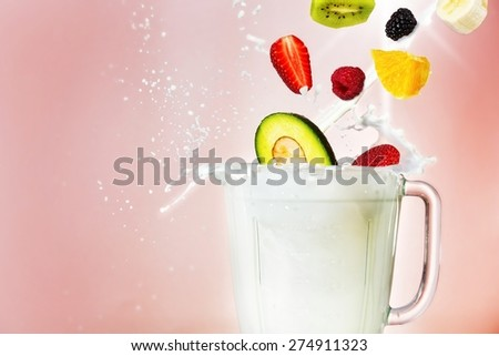 Smoothie concept. Milk/ yogurt and various fruits falling inside smoothie blander glass. - stock photo