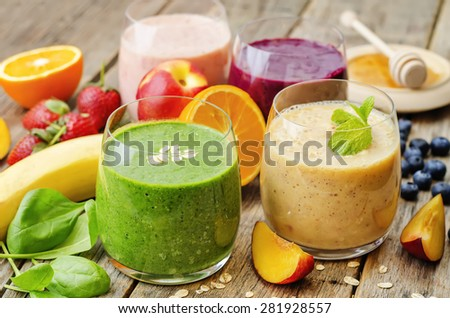 smoothie with spinach; blueberries, peach and strawberries. the toning. selective focus - stock photo