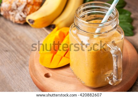 smoothie with tropical fruits: mango, banana, pineapple in a glass jar Mason on the old wooden background - stock photo