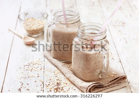smoothies with  oatmeal,  flax seeds in glass jars on a wooden background - stock photo