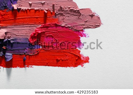 Smudged colourful lipstick on white background, close up - stock photo