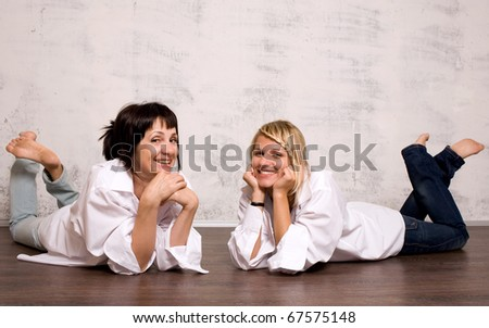 Smyling mother and dauther lying on the floor - stock photo