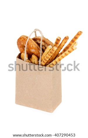 Snack bag hold in hand isolated on white. Delivery and sale of food. Cookie, bread and cracker in supermarket  package ready for logo design presentation.  - stock photo