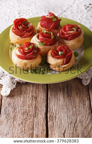 snack baked roll with salami and cheese in the form of roses on a plate on the table. vertical - stock photo
