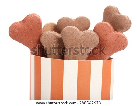 Snack food for dogs biscuits shaped as bone in striped box - stock photo