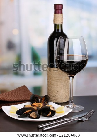 Snack of mussels with lemon and wine on plate on wooden table on room background - stock photo