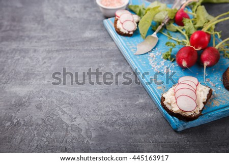 Snack,sandwiches with cheese and radishes on dark bread.Background on the blue Board.Healthy food or diet concept.top view.Copy space.selective focus. - stock photo