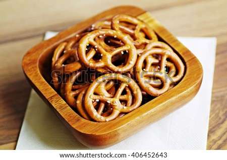 Snack. Snack food. Snack in wooden bowl. Salted pretzel snacks in wooden bowl. Closeup of pretzels in wooden bowl. - stock photo