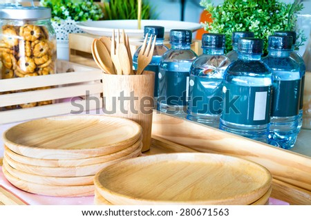 Snack time setting up with wooden plates, wooden cup, wooden fork and spoon with many plastic bottle and also a glass mug with pineapple biscuit inside - stock photo
