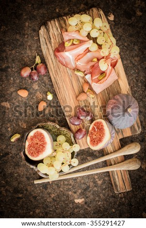 snacks for wine grapes in the form of dates and bacon - stock photo