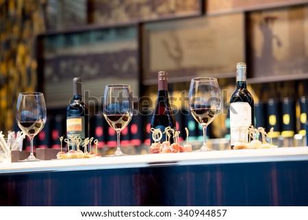 Snacks, glasses of wine and bottles on bartender counter in restaurant - stock photo