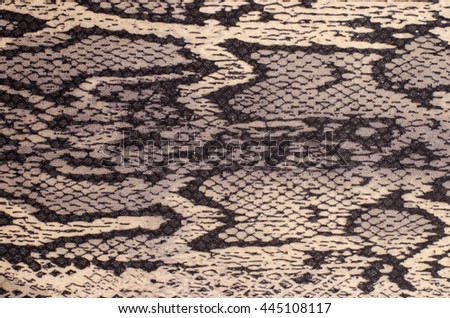 Snake skin pattern on fabric. Close up on black and brown snake skin print for background. - stock photo