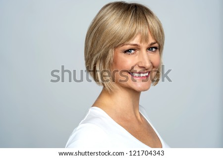 Snap shot of a cheerful blonde, side pose. Gray background. - stock photo