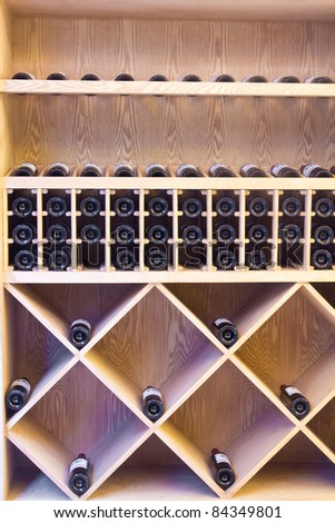 Snapshot of the wine cellar. The bottles on wooden shelves. - stock photo