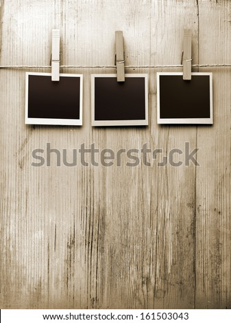 snapshots hanging from a rope on a wooden background - stock photo
