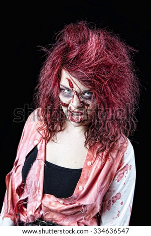 Snarling, red-headed zombie girl in bloody, tattered clothing.  Shot on black background. - stock photo