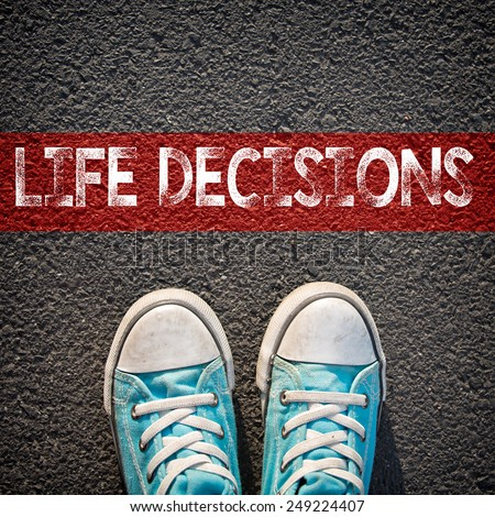 Sneakers and word life decisions. Male sneakers on the asphalt road with drawn word life decisions - stock photo
