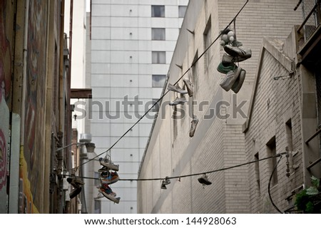 Sneakers hanging by the laces over powerlines - stock photo